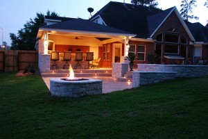 This fire pit by Outdoor Homescapes of Houston helps extend outdoor entertaining into the night with its warmth and glow near the covered patio with an outdoor kitchen, outdoor bar and grill area, retaining walls, stamped concrete hardscape and an outdoor media room. More at www.outdoorhomescapes.com