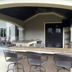 This covered patio features a wet bar, kegerator, grill and mounted TV. The roof extension matches the exterior of the home. too. This outdoor living space was designed by Outdoor Homescapes of Houston in Cypress, TX. For more ideas and inspiration, visit www.outdoorhomescapes.com