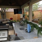 This covered patio features an outdoor kitchen with a sink, state of the art grills, a seating area and plants that echo the greenery of the backyard landscape. It was designed and built by Outdoor Homescapes of Houston in Cypress, TX. For more outdoor living designs and ideas, visit www.outdoorhomescapes.com.