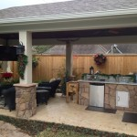 This covered patio and outdoor kitchen blends beautifully into the back yard landscape with its seating area and mounted flat-screen TV. It was designed and built by Outdoor Homescapes of Houston in Cypress, Texas. For more outdoor living space designs and ideas, visit www.outdoorhomescapes.com.