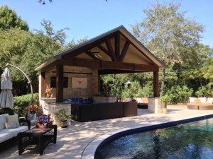The timber frame construction of this covered patio matches the home's architectural style and landscape. It also lends a cozy air to the seating area by the pool. It was designed and built by Outdoor Homescapes of Houston in Cypress, TX. For more outdoor living space designs, ideas and inspiration, visit www.outdoorhomescapes.com.
