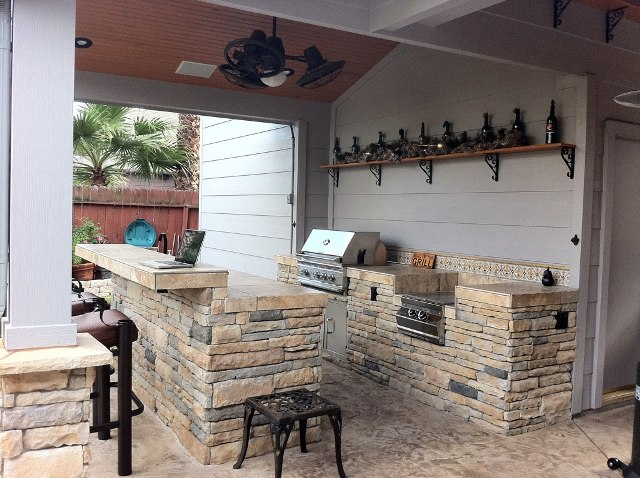 With its rustic shelf decorations, ceiling fan and natural stone island, this outdoor kitchen is one of the outdoor living spaces perfect for celebrating Go Texan Day 2014. For other outdoor living designs and ideas by Outdoor Homescapes of Houston, visit www.outdoorhomescapes.com.