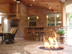 This fire pit, designed and built by Outdoor Homescapes of Houston, extends the outdoor living season - and your day - with its warmth and glow. This one is part of a warm, cozy, rustic covered patio with a slanted wood ceiling, an outdoor bar and grill area with an outdoor kitchen, patio seating, a tile floor and an outdoor media center, not to mention glowing pendant lamps. More at www,.outdoorhomescapes.com