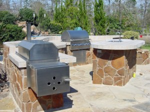 This outdoor kitchen by Outdoor Homescapes of Texas features a professional grade smoker built into a natural stone island. The outdoor living space also has a sink and a grill. For more outdoor living designs like this, visit www.outdoorhomescapes.com