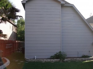Before shot. Back view of a garage from the back yard. A covered patio with an outdoor bar and grill area will come into the backyard from this garage, and another covered outdoor living space - a living room - will span the distance between the garage and the house to the right. For more on Outdoor Homescapes of Houston, go to www.outdoorhomescapes.com