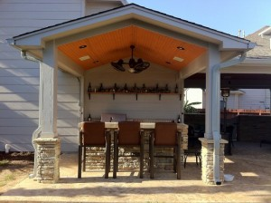 "Second ""after shot"" of outdoor living space design by Outdoor Homescapes of Houston. This covered patio, made possible by a roof extension with a wooden ceiling, features a rusting outdoor bar and grill area. More at www.outdoorhomescapes.com."