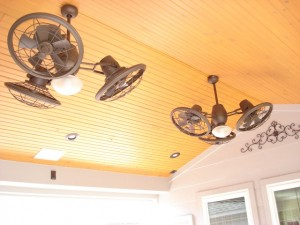 This a closeup of a wood ceiling with rustic styled outdoor ceiling fans on a patio cover and roof extension designed and built by Outdoor Homescapes of Houston. For more on this outdoor designer, go to www.outdoorhomescapes.com