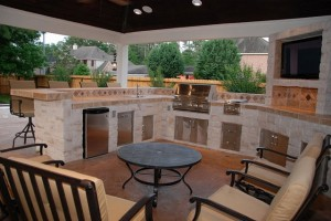 "High-end covered outdoor kitchen with dishwasher, RCS 30"" grill, double burner, refrigerator, sink, bar and trash drawer. Built by Outdoor Homescapes of Houston, an outdoor living space design company in Cypress, TX. More projects like this at www.outdoorhomescapes.com"