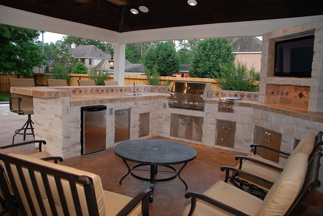 "Houston outdoor living spaces like this with a TV and bar area are prime real estate for fans wanting to watch the game during football season. High-end covered outdoor kitchen with dishwasher, RCS 30"" grill, double burner, refrigerator, sink, bar and trash drawer. Built by Outdoor Homescapes of Houston, an outdoor living space design company in Cypress, TX. More projects like this at www.outdoorhomescapes.com"