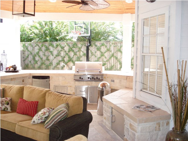 This Houston outdoor living space comprises a covered patio via roof extension with an outdoor kitchen, outdoor living room, outdoor bar and grill area and bench storage. To see the blog post this images was part of, go to http://www.outdoorhomescapes.com/outdoor-living-spaces-boost-quality-life-home-values/. To see more outdoor living spaces designed and built by Outdoor Homescapes of Houston, go to www.outdoorhomescapes.com.