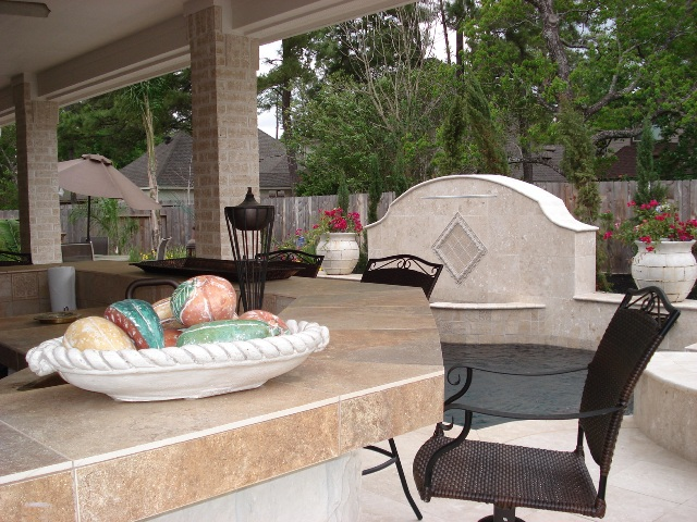This image of a Houston outdoor kitchen shows a nice tile counter, a water feature (fountain) and counter seating. It's part of a blog post at http://www.outdoorhomescapes.com/outdoor-living-spaces-boost-quality-life-home-values/. For more outdoor living spaces by Outdoor Homescapes of Houston, go to www.outdoorhomescapes.com.