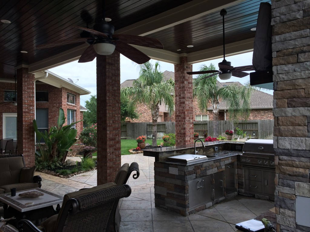 This covered patio addition by Outdoor Homescapes of Houston features high wood ceilings, a gas fireplace with a TV and seating area and an outdoor kitchen. More at www.outdoorhomescapes.com