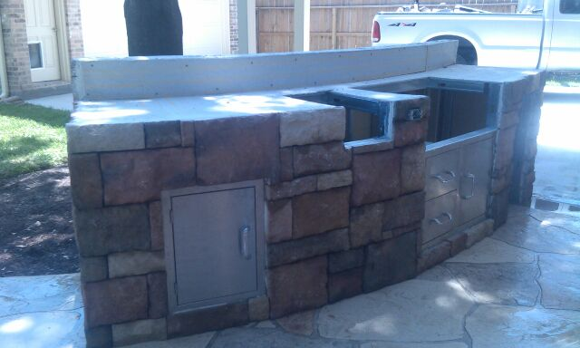This small outdoor kitchen with a curved back, built by Outdoor Homescapes of Houston, needed a galvanized steel frame, covered with HardiePanel and then drystacked limestone. More at www.outdoorhomescapes.com.