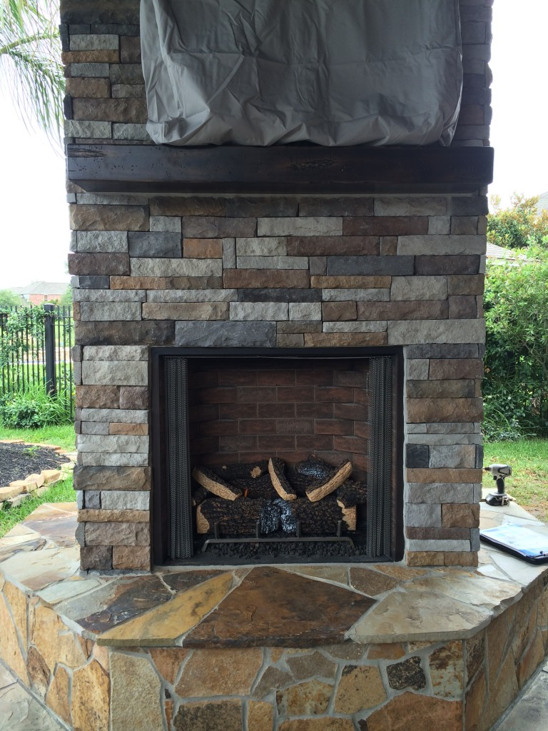 This gas-burning fireplace features a mounted flat-screen TV, drystacked ledgestone walls, a wooden mantel and a flagstone hearth. Designed and built by Outdoor Homescapes of Houston. More at www.outdoorhomescapes.com/blog