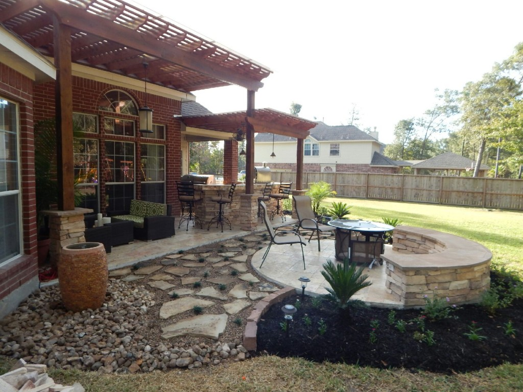 A two-tier pergola, circular firepit area and outdoor kitchen with a Fire Magic charcoal-gas combo grill are featured in this Houston patio design by Outdoor Homescapes of Houston. More at www.outdoorhomescapes.com/blog
