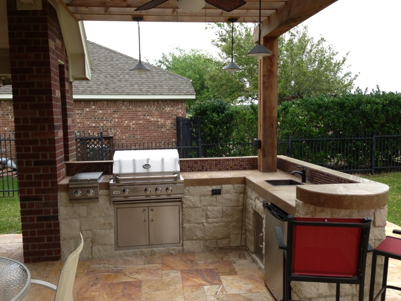 This Houston patio addition features a double pergola and outdoor kitchen with a curved raised bar and travertine tile. More at www.outdoorhomescapes.com/blog