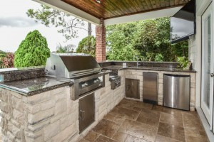 This Houston remodel by Outdoor Homescapes of Houston features an outdor kitchen with a Titanium granite countertop, a travertine tile floor, French doors, a 50-inch outdoor TV and an RCS grill and appliances. More at www.outdoorhomescapes.com/blog