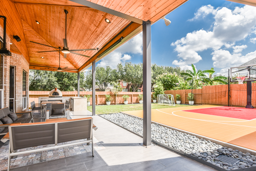 This unique Houston patio features a French drain next to a basketball court. More details on this patio project at www.outdoorhomescapes.com/blog